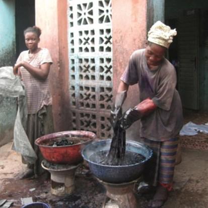 Farbfoto: junge Frauen färben im Freien Kleidung schwarz, Färbeschüsseln stehen zum erhitzen auf tönernen Stöfchen