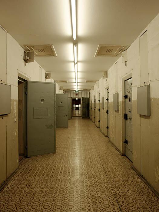 Farbfoto: Blick in den Gefängnistrakt; einige Türen stehen offen