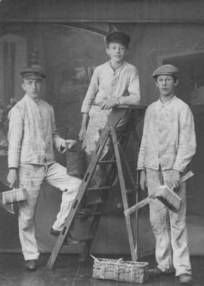 s/w-Foto: drei Jugendliche in Malerkleidung mit Malerpinsel; einer von ihnen steht auf einer Leiter