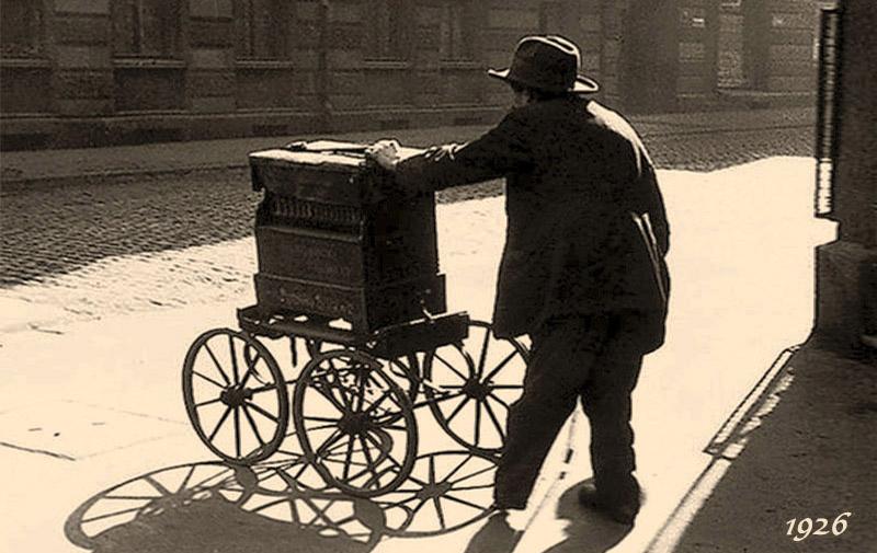 altes s/w Foto: alter Mann mit Leierkasten auf vier Rädern auf Kopfsteinpflasterstraße im Gegenlicht