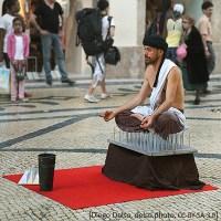 Farfoto: Auf Nagelbrett sitzender Mann in einer Einkaufspassage - 2012