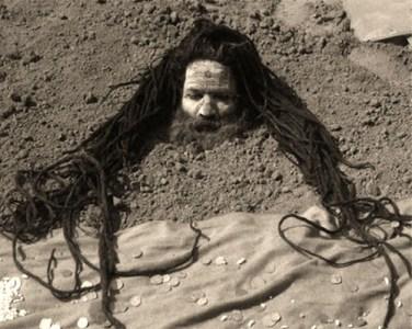 sw Foto: Mann mit sehr langem Haar steckt bis zum Hals in der Erde