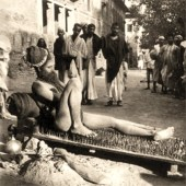 sw Foto: auf Nagelbett halbliegender Fakir in städtischem Umfeld