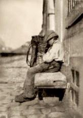 sw Foto: Lumpenjunge sitzt eingeschlafen auf Steinbank neben seinem Rückenkorb