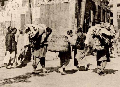 sw Foto: Männer und Frauen, die große Körbe und Lumpenbündel auf dem Rücken tragen
