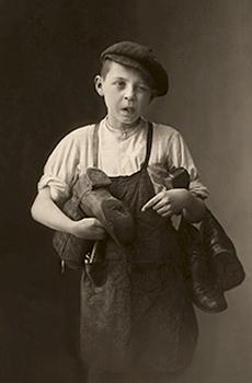 sw Foto: kleiner Schusterlehrling mit kaputten Stiefeln unterm Arm - 1910