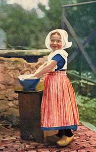 Farbfoto: kleines Mädchen in Holzschuhen mit Waschschüssel neben Brunnen