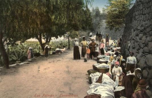 nachkoloriertes Foto: Ansammlung waschender Frauen an Wasserlauf vor Bruchsteinwand
