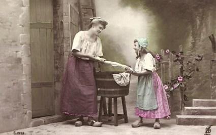 AK: Frau und Mädchen beim Auswringen von Wäsche