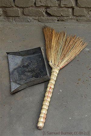 Farbfoto: Handbesen und Kehrblech am Boden liegend