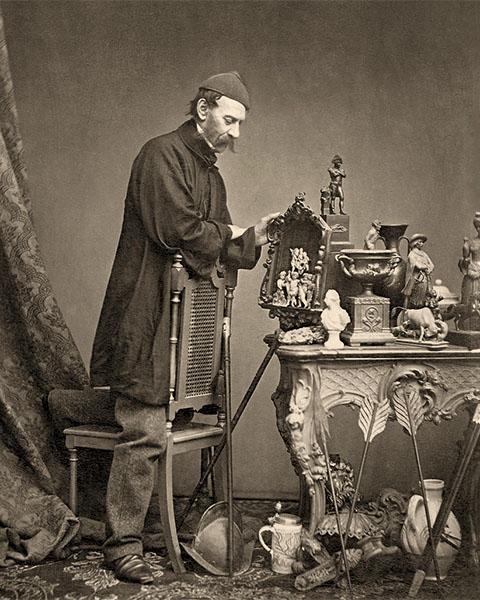 sw Foto: Händler hat vor sich auf einem antiken Tisch und um diesen herum seine Schätze drapiert