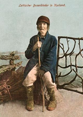 koloriertes Foto: alter Besenmacher, auf Holzblock sitzend, ein Reisigbündel neben sich am Boden