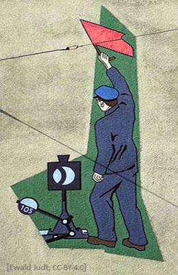 farbiges Wandbild: Bahnwärter mit erhobener Flagge neben Weichenhebel