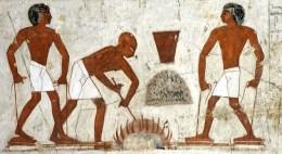 Wandmalerei: zwei Männer betätigen kleine Fußblasebälge, mittig arbeitet einer am Schmelzfeuer