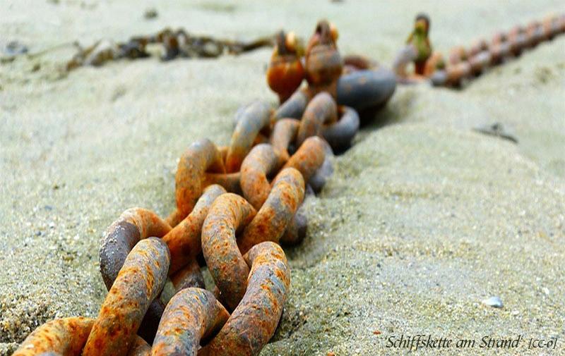 Farbfoto: Kette im Sand liegend
