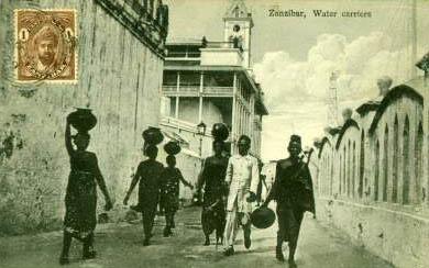 Postkarte: mehrere Menschen tragen Wasser in Gefäßen auf ihren Köpfen