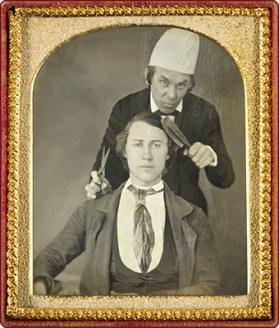 sw Daguerreotype in Goldrahmen: Barber mit Schere und Bürste hinter Kunde stehend