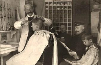 sw Postkarte: einem Herr wird das Haar kurz geschnitten, weitere Kunden warten Zeitung lesend - 1915