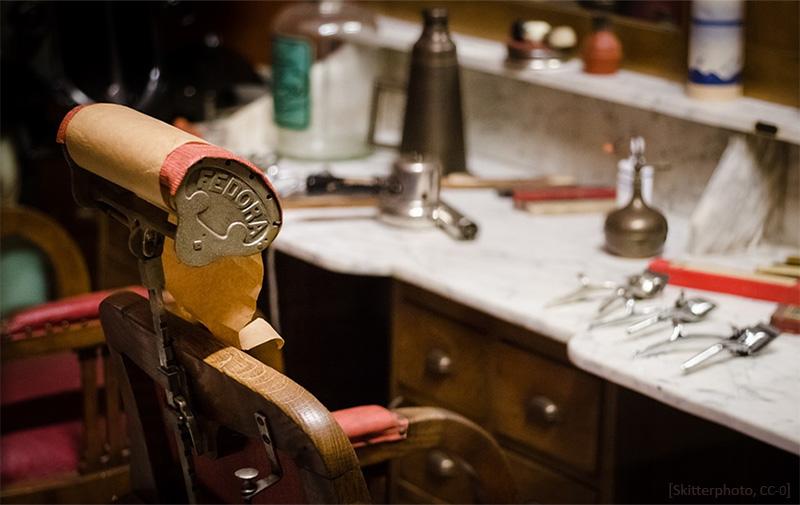 Farbfoto: historischer Kundenstuhl vor Frisiertisch mit Utensilien