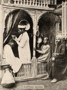 sw Postkarte: Araber schneidet Kunden das Haar, ein Junge hält Handspiegel, daneben Mann mit Wasserpfeife
