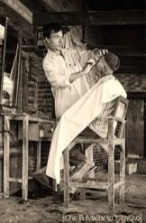 sw Foto: nepalesischer Friseur bedient auf hohem Hozszuhl sitzenden Kunden - 2010