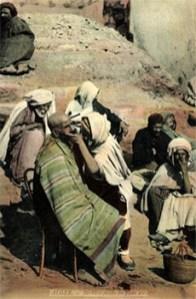 kolorierte Postkarte: Freiluftbarbier in einer Gruppe von Männern