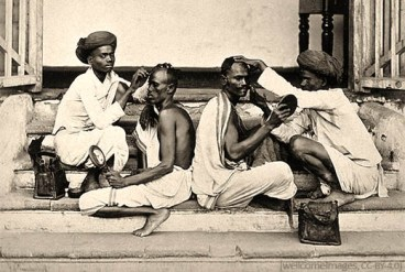 sw Postkarte: zwei Rücken an Rücken auf Steinstufen sitzende Inder lassen sich Haare schneiden - 1920