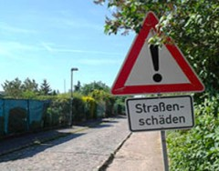 Farbfoto: Straße mit Kopfsteipflaster + Schild 'Straßenschäden!'