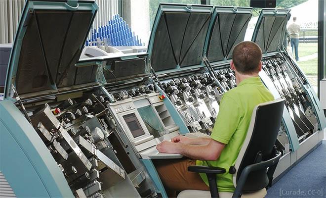 Farbfoto: Mann bedient computergesteuerte Geldzählmaschine - 2017