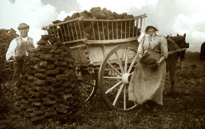 altes Foto: Frau und Mann laden Torfstücke auf einen Pferdekarren