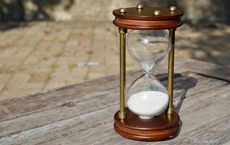 Farbfoto: Stundenglas auf Holzplatte