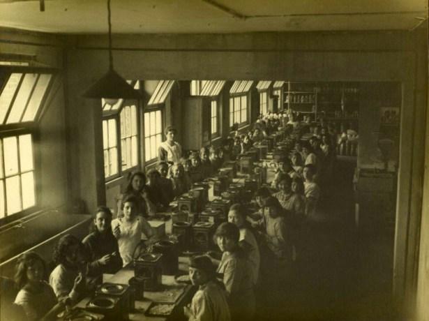 Foto: Mädchen und Frauen am langen Tisch verpacken Bonbons