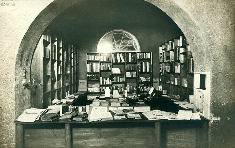 Foto: Buchhändler sieht in einem Gewölbe zwischen Büchern