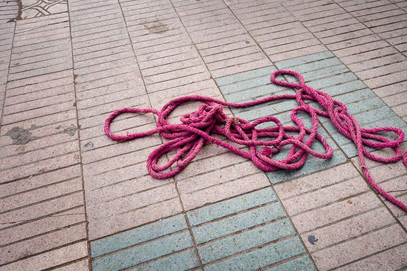 Foto: himbeerfarbenes Seil auf Boden liegend