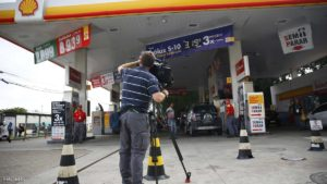 A television cameraman films at the gasoline station where U.S. swimmers Ryan Lochte, Jimmy Feigen, Jack Conger and Gunnar Bentz were accused by staff of having caused damage, in Rio de Janeiro, August 18, 2016. REUTERS/Nacho Doce