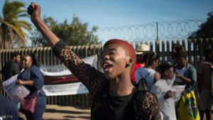 """A woman gestures during a protest against ongoing violence against women, in Gugulethu, on May 21, 2016, about 20 Km from the centre of Cape Town. This protest march, one of two organised in Cape Town for the day, is part of the international """"Walk a mile in her shoes"""" project, where people march to raise awareness of this issue, and asking men and boys, in particular, to wear high heels, to show their solidarity with women. South Africa has, proportionally, one of the highest rates of rape in the the world, with more than 60000 cases of sexual assault being reported in 2015(according to South African Police statistics). / AFP / RODGER BOSCH        (Photo credit should read RODGER BOSCH/AFP/Getty Images)"""
