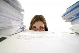 woman looking at piles of paperwork
