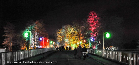 The village of Osthouse is near the river Ill. The Christmas Trails are spreading over left and right banks of the river. Colorful lanterns are illuminating the bridge.
