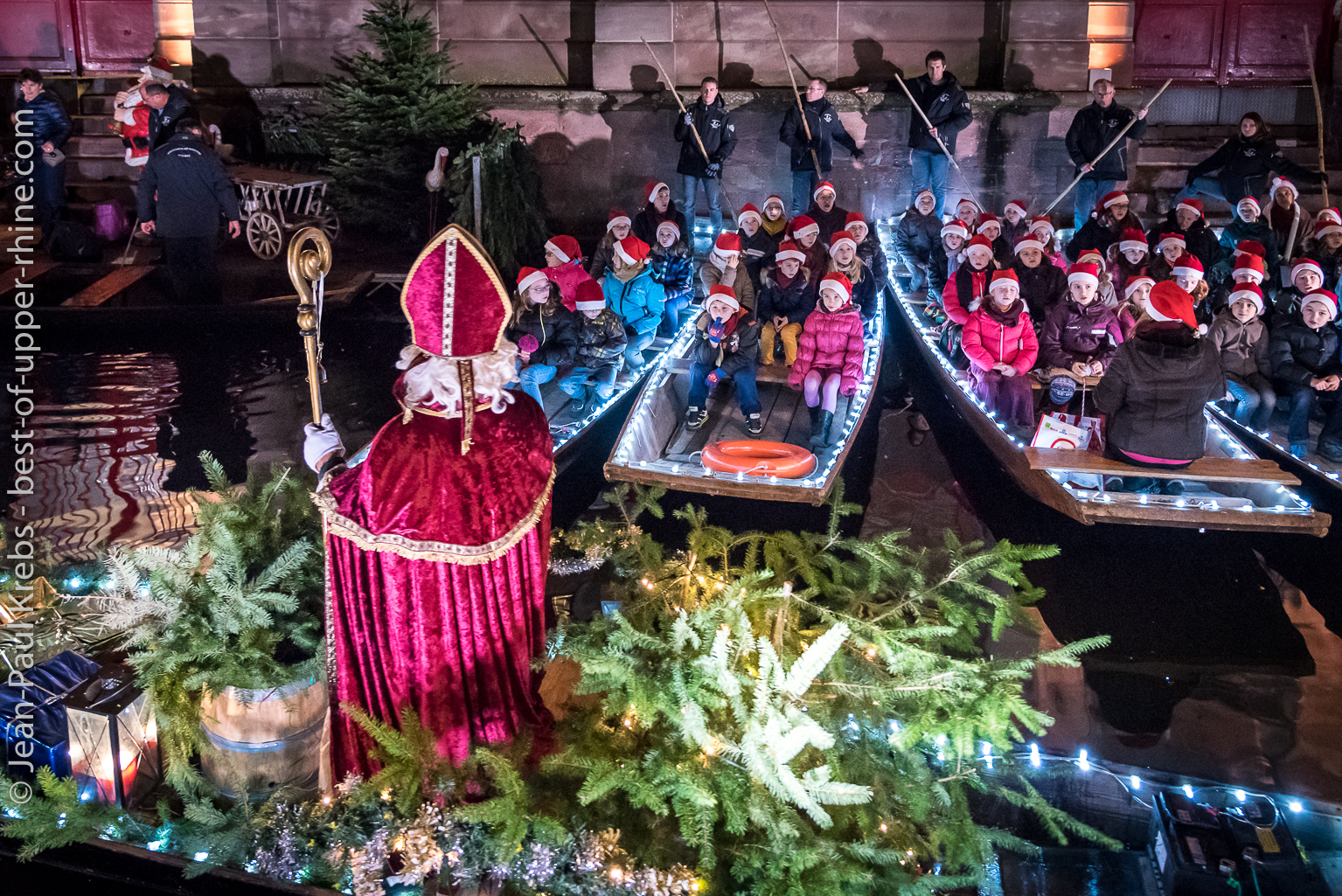 Saint Nicholas is arriving with a small boat and cheered by singing children.