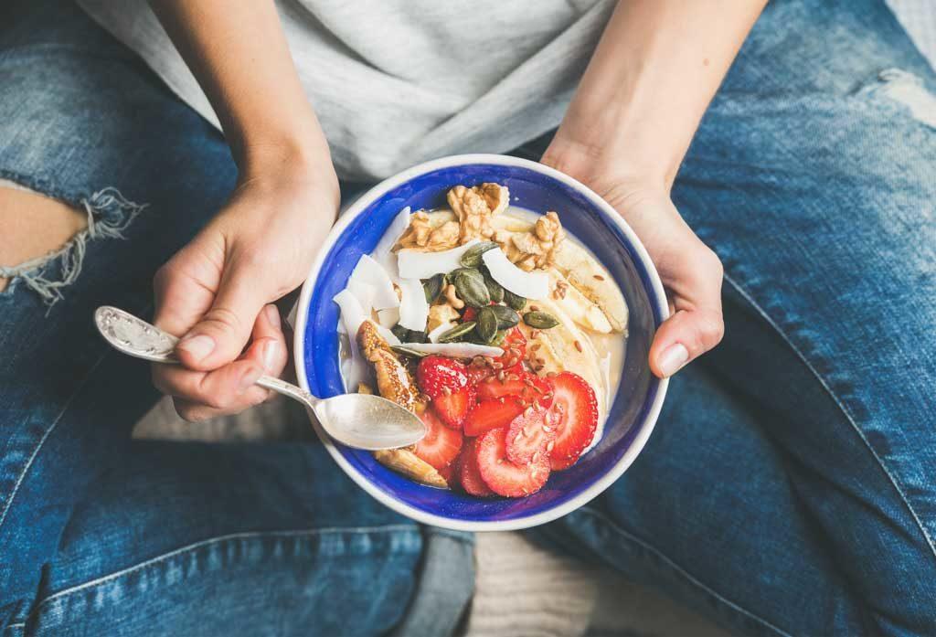 Was ist die beste Diät?Gesunde Frühstücksschüssel essen. Joghurt, Müsli, Samen, frische und trockene Früchte und Honig in blauer Keramikschale in Frauenhänden. Sauberes Essen, Diät, Entgiftung, vegetarisches Ernährungskonzept