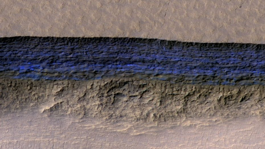 For the first time, high-resolution images show the three-dimensional structure of massive ice deposits on Mars. This photo by the HiRISE camera aboard NASA's Mars Reconnaissance Orbiter shows a detailed subsection of an icy scarp on the Red Planet in enhanced color.