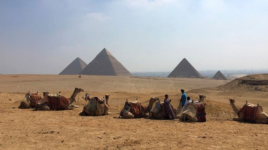 Camels rest between rides with their owners against the backdrop of the pyramids in Giza, Egypt, in 2015.