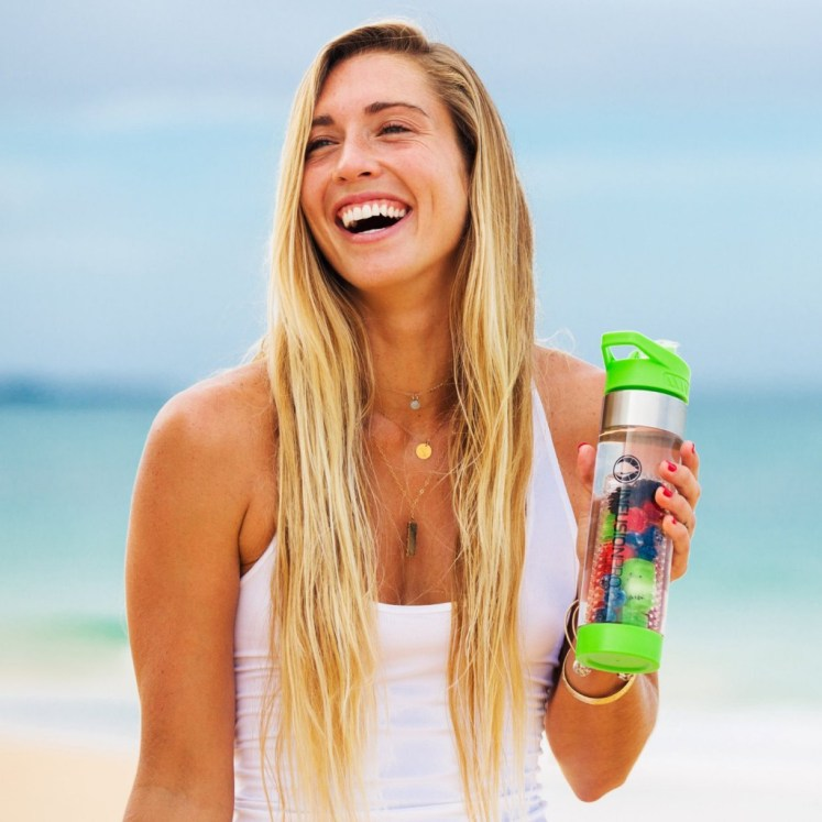 A girl is holding an Infusion Pro Premium bottle, the infusion pro is one of the best infuser water bottle. The is smiling big time, and it is sunny outside.