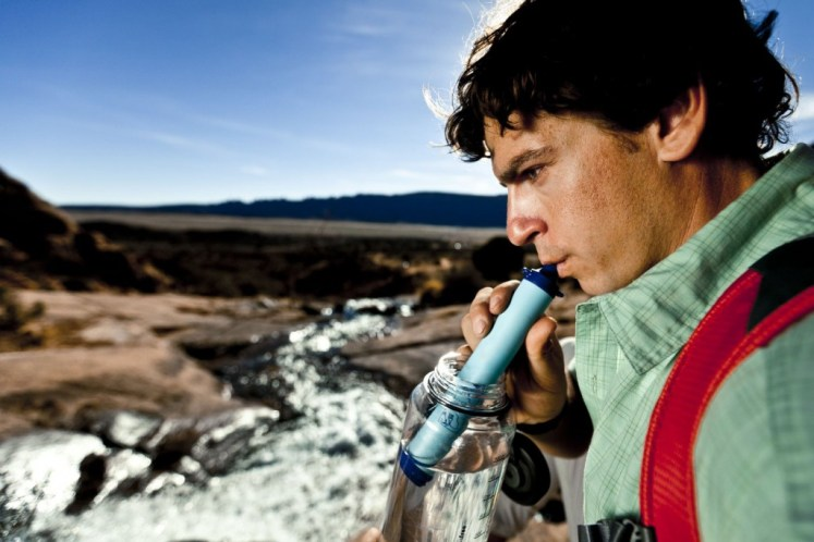 man drinking with lifestraw from bottle