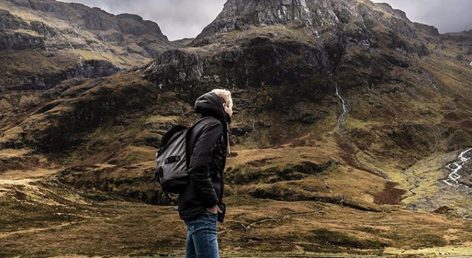 man wearing a backpack standing on a mountain