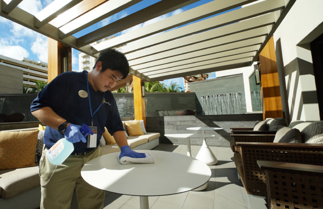 Matthew Sakamoto wipes down tables at Hokulani timeshare.