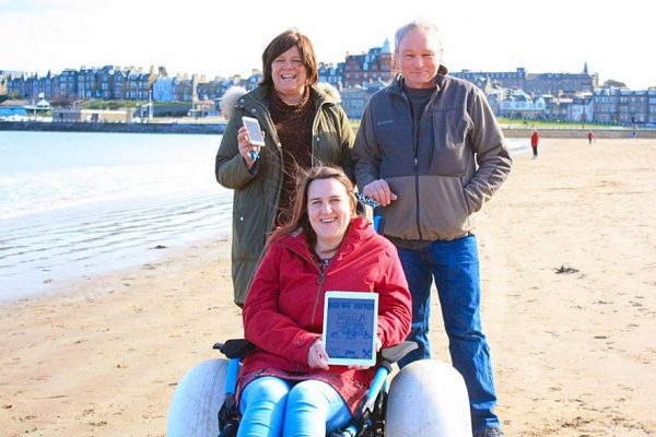 Amy Newton of MS Society Fife using one of the St Andrews Beach Wheelchairs and viewing the Scotland's Accessible Beaches App. From left to right Debbie McCallum (left), Amy Newton (centre), Peter Newton (right)