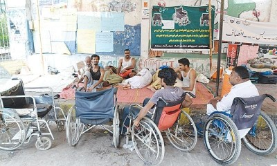 Group of persons with disabilities sitting together with some empty wheelchairs around.