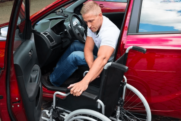 A man in a car getting off and trying to open a wheelchair
