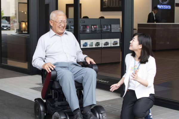 A man seated on a wheelchair and a woman kneeling smiling at him
